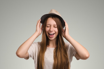Positive casual woman posing. Emotional girl portrait. Young female with hat. The model with closed eyes screaming.