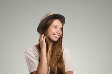 Positive casual woman posing. Emotional girl portrait. Young female with hat. The model is looking away.