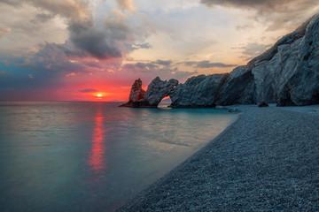Kiesstrand am Mittelmeer mit Felsen bei dramatischen Sonnenaufgang