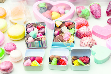 photo handmade soap in the form of sweets, heart, canteen, fruit, in boxes on the table close-up as background under the inscription