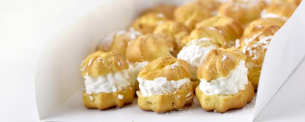 Profiteroles or cream puff cakes in white paper box