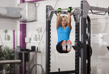 Bodybuilding. Strong fit woman exercising in a gym - doing pull-ups.