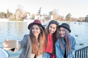 Philippine women taking photos and selfie in Retiro Park Madrid