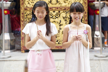 Two girls praying in a temple
