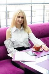 Красивая молодая девушка со светлыми волосами сидит в кафе за столиком на малиновом диване с чашкой кофе