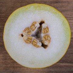 Half of melon on the wooden background, top view