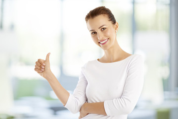 Successful young woman giving thumbs up