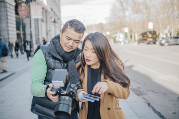 Chinese Couple checking pictures around Palacio Real of Madrid