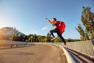 A girl runner in a superhero costume jumps on the road. The concept of success in sports. Healthy lifestyle.