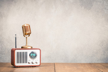 FM radio receiver and golden microphone front concrete wall background. Listening music concept. Vintage old instagram style filtered photo