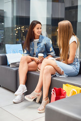Portrait of two beautiful young women chatting in shopping mall, sitting on bench in hall relaxing with coffee