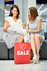 Portrait of two happy women in shopping mall, looking at blouse bought on SALE, red paper bag in foreground