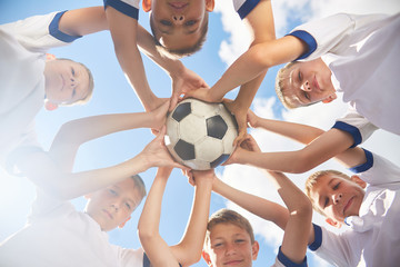 Low angle view of boys in junior football team standing in circle holding ball together and looking at camera against blue sky