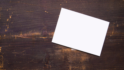 a white blank postcard template for graphic design on a wooden background