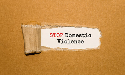 The text STOP Domestic Violence appearing behind torn brown paper