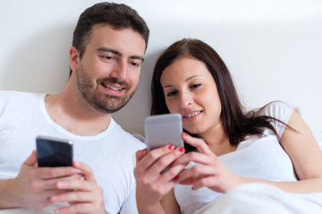 Happy couple using mobile phone lying in bed