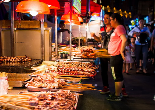 NANNING, CHINA - JUNE 9, 2017: Food on the Zhongshan Snack Street, a food market in Nanning with many people bying food and walking around
