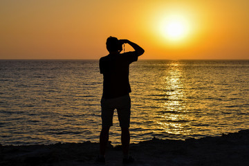 Silhouette of a man taking photos of the sunset over the Mediterranean Sea from Formentera Island, south of Ibiza Spain