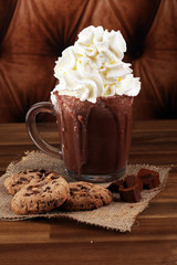 A messy cup with hot chocolate and chocolate chip cookies.