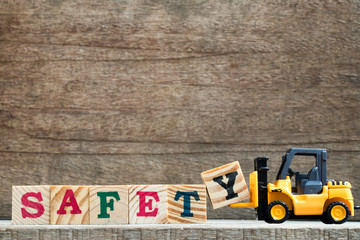 Toy plastic forklift hold block Y to compose and fulfill wording safety on wood background