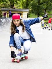 Cute girl in a baseball cap with a skateboard in a skate park. Sports.