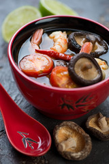 Close-up of a red bowl with spicy Tom Yum soup, selective focus, vertical shot