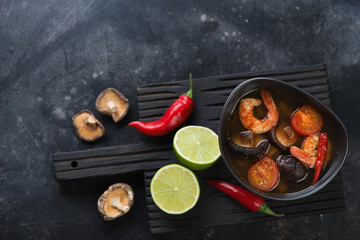 Hot Tom Yum soup with some of its cooking ingredients on a dark scratched metal background, flat-lay with space