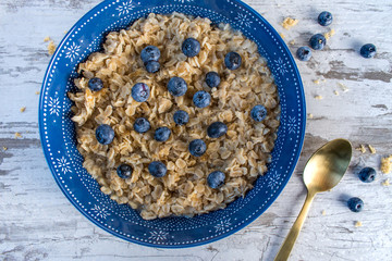 Oatmeal with Blueberries in blue bowl on rustic table