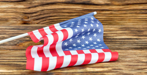 Small American flag on wooden background. Close up.