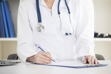Doctor in a white labcoat writing