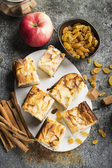 A simple homemade pie with apples and sour cream on a gray background with cinnamon sticks, an apple, caramel sweets. Top view. Selective focus.