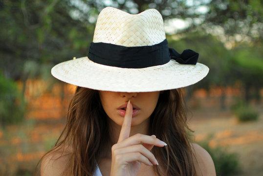 chica joven con sobrero y con un dedo en sus labios indicando silencio
