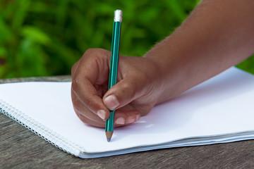 black kid's hand draws in pencil