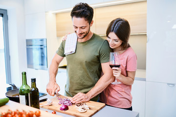 Cute young girlfriend hugging boyfriend as he prepares vegetables for dinner in the kitchen