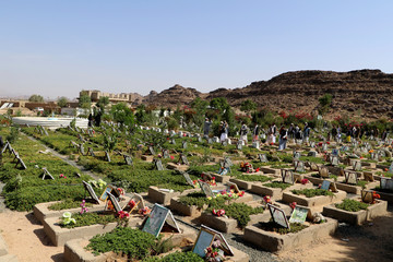 People visit a graveyard allocated for Houthi fighters killed in the ongoing Yemeni conflict in the northwestern city of Saada