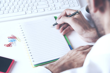 Asia business man hand using laptop and writing note pad on table