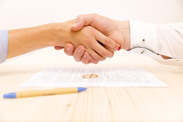 Closeup of a young man an a young woman shaking hands after signing a prenuptial agreement