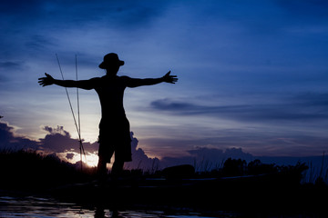 Silhouette traveler man relaxing on the beach with fishing rod and raise hand him arms open felling freedom.