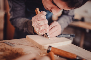 Wood processing. Joinery work. wood carving. The carpenter uses a cutting knife for framing