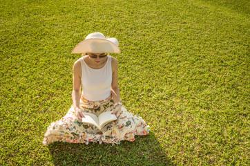 Linda mulher lendo livro em gramado verde.