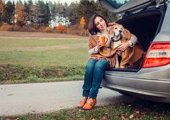 Woman with dog sit together in cat truck and warms hot tea