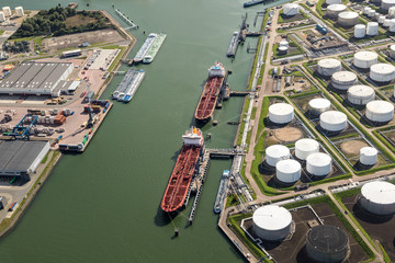 Tankers moored at an oil terminal with storage silo's in the Port of Rotterdam.