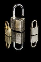 Three small metal locks om a reflective surface