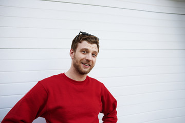 Handsome young red-haired European hipster guy with fuzzy beard wearing red sweatshirt and sunglasses on his head posing against white background and looking at camera with cheerful excited smile