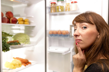 Confused young woman looking in fridge at kitchen