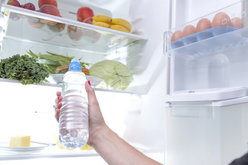 Woman taking a water bottle out of the fridge