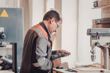 Image of carpenter using electric drill.