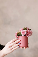 Beautiful pink roses in crimson cup holding in hands on beige wall. Festive background of love, early spring gift and blossom concept, free space above