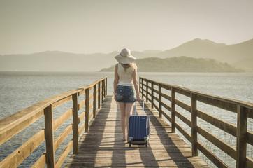 Ótimo conceito de viajar, férias, mulher caminhando com bagagem em doca, esperando o navio para viajar.