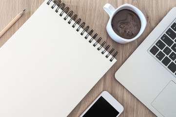 Image of blank notebook paper space, cellular phone, laptop computer and coffe neatly arranged on wooden table